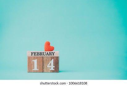 Wooden calendar show of February 14 with red heart on pastel color background.
