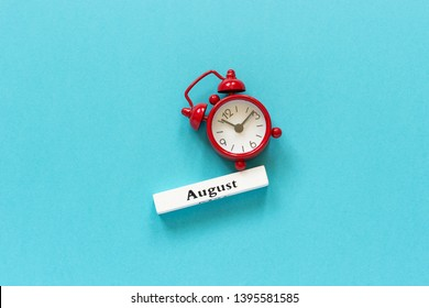 Wooden calendar summer month August and red alarm clock on blue paper background. Concept Hello August or Good bye August Creative Top view Flat Lay Minimal style.
