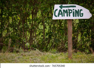 A wooden camping hand painted sign with the arrow pointing to the left