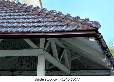 wooden canopy of white bars of wood with brown tiles.