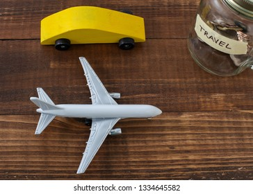 Wooden car with airplane and coins in jar with travel label