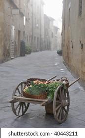 Wooden cart in medieval marketplace scene in Italian Piazza
