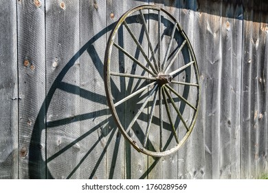 wooden cartwheel shading on the plank wall of a barn