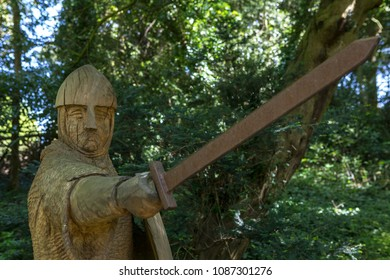 A wooden carved sculpture of an 11th Century soldier with armour, sword and shield at Battle Abbey in East Sussex, UK.  Battle Abbey is on the sight of the 1066 Battle of Hastings battlefield.