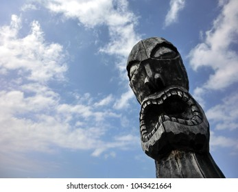 Wooden carved tiki head totem against blue sky