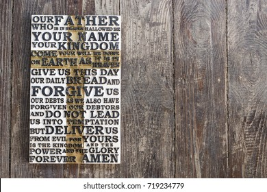 Wooden carved word of the Lord's Prayer on the  dark  brown shabby wooden  plank  background.