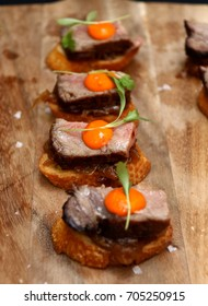 Wooden carving board with beef tenderloin with egg yolk hors d'oeuvres