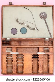 A wooden case of  old trial lenses set for a phoropter used for eye exam , circa 1940, top view