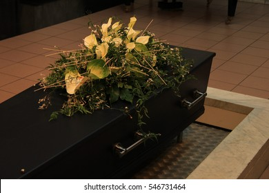 Wooden casket with funeral flowers, cremation ceremony