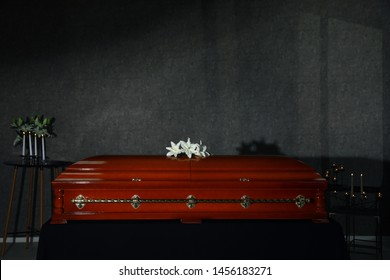 Wooden casket with white lilies and burning candles in funeral home