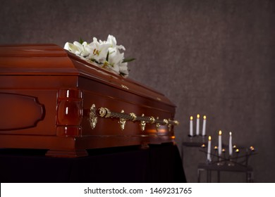 Wooden casket with white lilies in funeral home