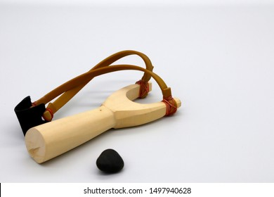 wooden catapult sling and black stone on white background