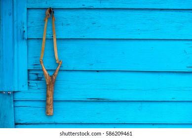 Wooden catapult slingshot hanging on blue wood background