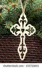 Wooden Cathedral Cross A laser cut wooden cathedral cross hanging from twine. The background of the image is fresh cut pine, and wicker weaving.