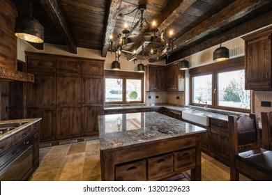 Wooden ceiling, retro chandelier and countertop in kitchen inteior