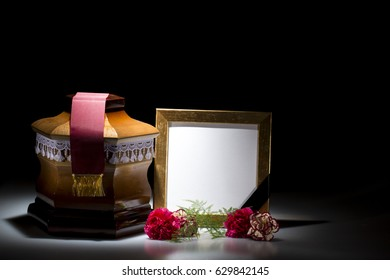 Wooden cemetery urn with blank mourning frame and carnation flower on dark background