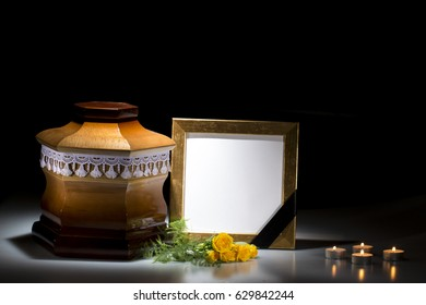 Wooden cemetery urn with blank mourning frame and yellow rosesand candles on dark background