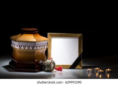Wooden cemetery urn with blank mourning frame and flower and candles  on dark background