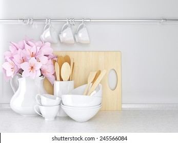 Wooden and ceramic utensils with flowers on the white marble worktop.