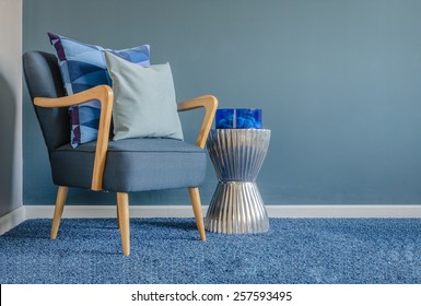 wooden chair with blue color pillow on carpet in living room