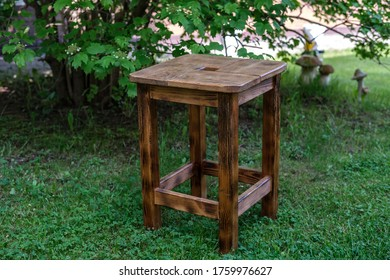 A wooden chair, burned with a gas burner and varnished, made by hand, stands on the grass in the garden.