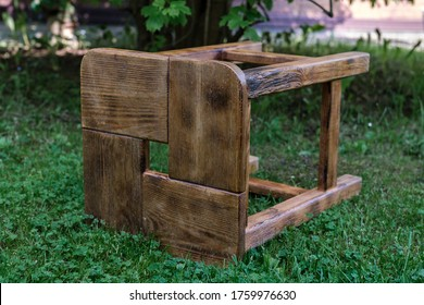 A wooden chair, burned with a gas burner and varnished, made by hand, lies on the grass in the garden.