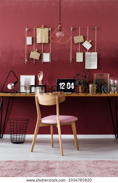 Wooden chair at desk with laptop against dark pink wall with notes in woman's workspace interior