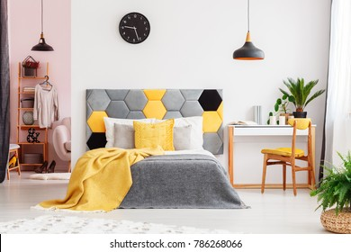 Wooden chair at desk with plant next to grey and yellow bed against white wall with clock in bedroom interior with wardrobe
