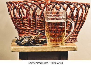 The wooden chair is a glass of foamy beer with a fish on the background of the Crimean basket of vines