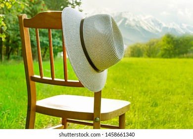 Wooden chair and a hat in the garden with view on mountain range in the distance. Summer holiday leisure idea.