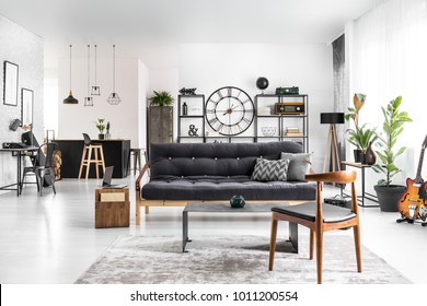 Wooden chair next to table and dark settee in spacious apartment interior with guitar and plants. Kitchen island in the background