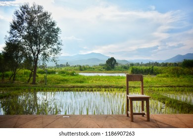 Wooden chair on the concreate floor placed at right of frame with panorama nature view at the Northern of Thailand on background.