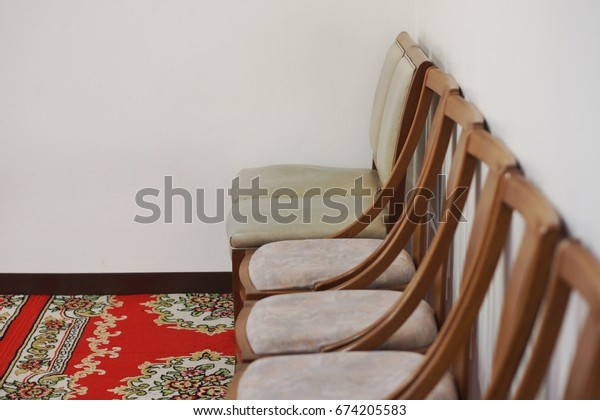 Wooden chair placed in front of cream colored walls. Red carpet