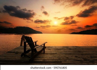 wooden chair situate on the balcony of the beach house with the sunset background