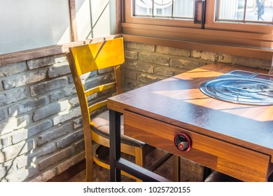 Wooden chair and table with electric stove. Furniture set for modern restaurant.