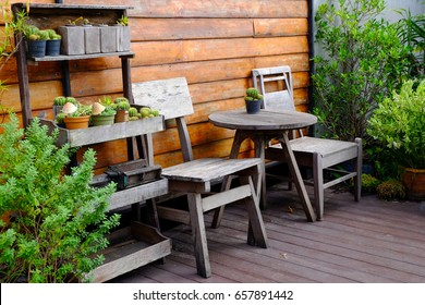 Wooden chair and table or wooden sofa set with trees next to the wooden wall in retro style.