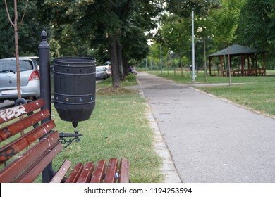 A wooden chair and a trash bin in the local park
