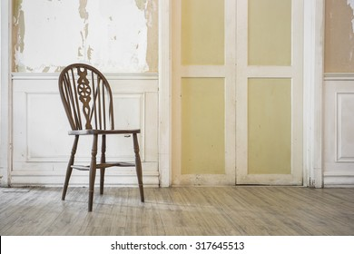 wooden chair in vintage old room with peeled off paint and grunge wallpaper