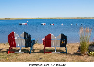 Wooden chairs along the shore and boat decorations on the water painted in the colors of the French Acadian flag on the coast near Bouctouche New Brunswick in the Canadian Maritime Provinces