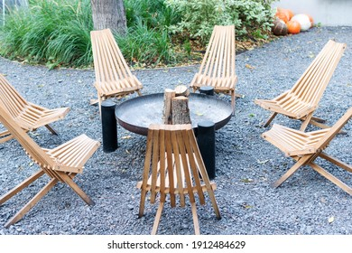 Wooden chairs arranged in a circle. Resting place with fireplace and chairs around.