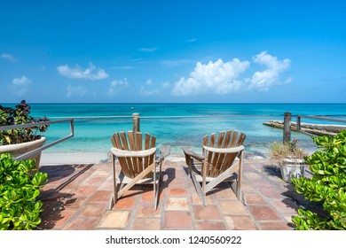 Wooden chairs facing the clear tropical ocean, vacation concept