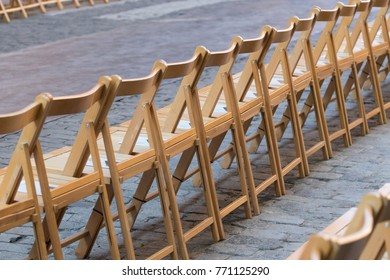 Wooden chairs on a row in the street.