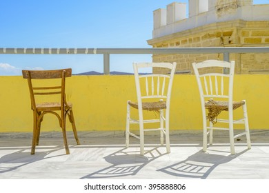 Wooden chairs on a terrace during summer. Bright sunlight and beautiful view.