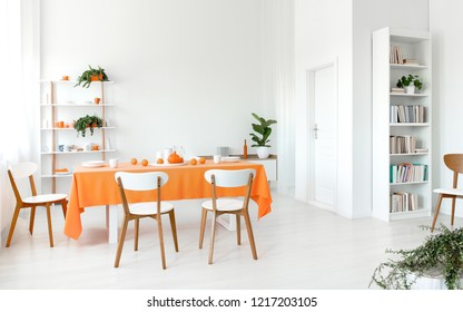 Wooden chairs at orange table in white dining room interior with plants on shelves. Real photo
