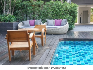wooden chairs and sofa for seat at poolside in luxury hotel
