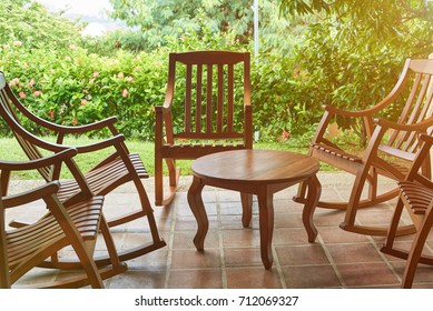 Wooden chairs and table in house terrace on summer background