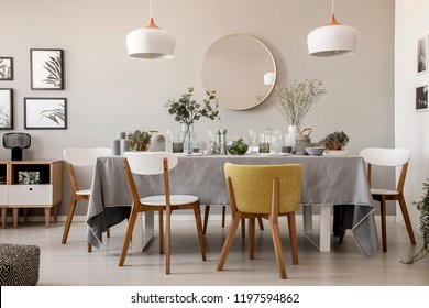 Wooden chairs at table with tableware in dining room interior with lamps and round mirror. Real photo