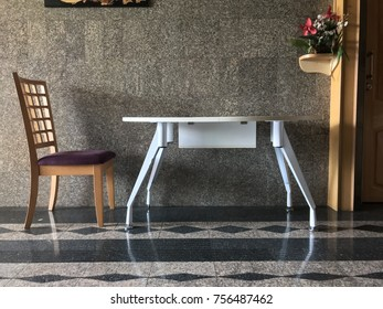 Wooden chairs and white table on granite tiled floor