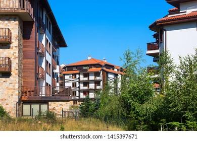 Wooden chalet hotel houses and summer panorama in bulgarian all seasons resort Bansko, Bulgaria
