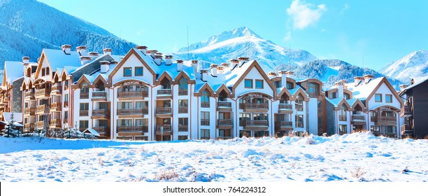 Wooden chalet, houses and snow mountains landscape and ski slopes panorama in bulgarian ski resort Bansko, Bulgaria